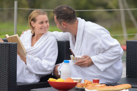 couple in bathrobes sat outdoors embracing at breakfast time