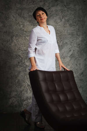 blouses: Portret woman in white dress next to the chair Stock Photo