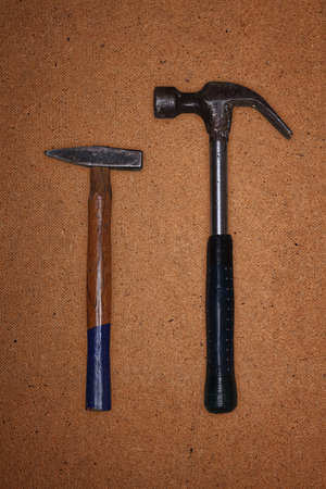 hardboard: Image of a hammer and nail puller, which lie on the hardboard