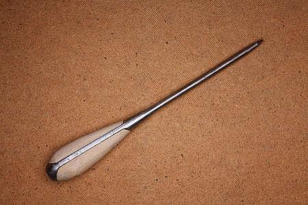 hardboard: Image of old-fashioned screwdriver lying on hardboard