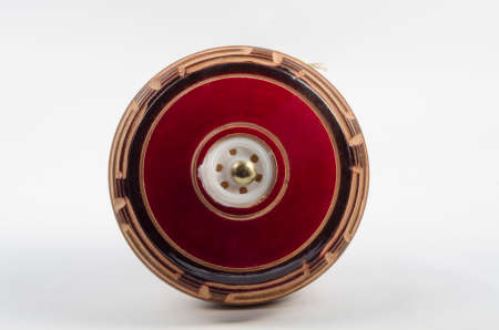 play yoyo: Vintage red and brown wooden yoyo on white background