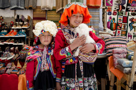 pisac: PISAC, PERU OCTOBER 6, 2015: Unidentified children with a lamb at Pisac market in Peru. Pisac is a well Known for STI village market every Sunday, Tuesday and Thursday.