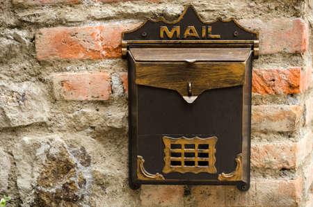 Brown metallic vintage mailbox on a brick wall