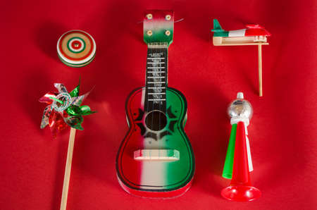 Yo yo, toy windmill, guitar, toy trumpet and noisemaker against red background. Accessories for mexican Independence Day celebration