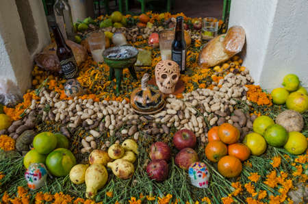 OAXACA, OAXACA, MEXICO- NOVEMBER 1, 2017: Traditional mexican Day of the Dead offering altar with fruit,flowers,sugar skulls and ornaments in Oaxaca, Mexico Publikacyjne