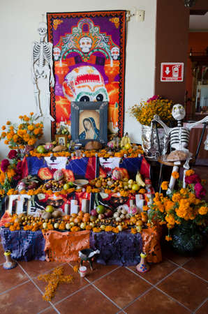 OAXACA, OAXACA, MEXICO- NOVEMBER 2, 2017: Traditional offering altar with four levels, yellow flowers, religious pictures, fruit,bread and a skeleton, part of the mexican Day of the Dead celebration in Oaxaca, Mexico Redakční