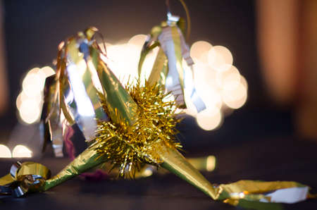 Yellow pinata as decoration for Christmas and New Year on bokeh background
