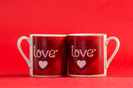 Two mugs with the word love and a little heart against red background. Valentines Day