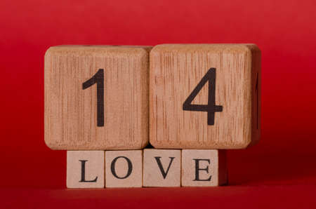 Big wooden cubes forming the number fourteen and little wooden cubes forming the word love against red background for Valentines Day Stok Fotoğraf