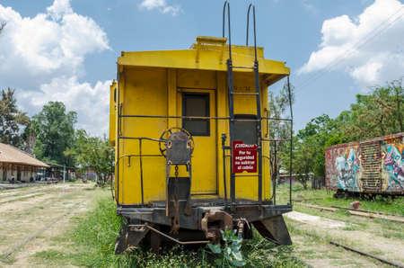 OAXACA, OAXACA, MEXICO- JUNE 1, 2018: Old rusty railway yellow carriage in a sunny day at Railway Museum in Oaxaca, Mexico