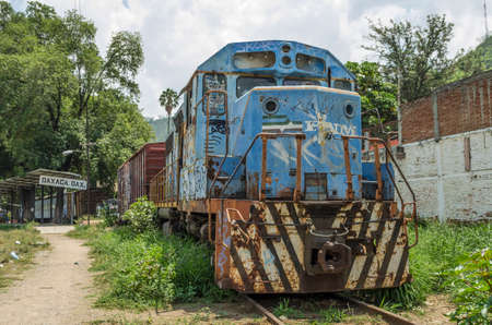 OAXACA, OAXACA, MEXICO- JUNE 1, 2018: Old rusty blue train in a sunny day at Ferrocarril Museum in Oaxaca, Mexico