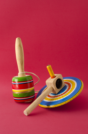 Balero and spinning against red background. Wooden mexican toys against red background