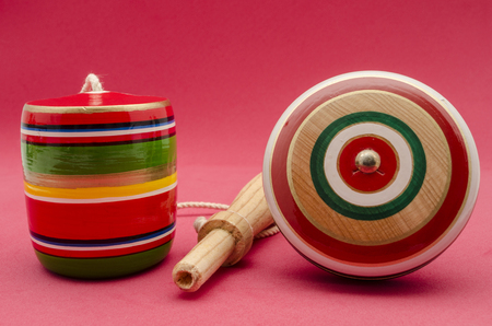 Colorful balero and me yo against red background. Mexican wooden toys