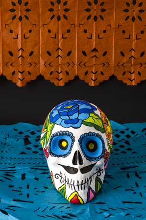 Styrofoam skull with flowers and mustache in a day of the dead offering altar with orange and blue cut paper