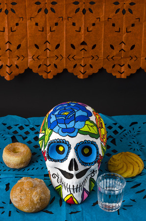 Styrofoam skull with flowers and mustache in a day of the dead offering altar with orange and blue cut paper, bread and mezcal