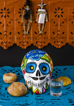 Styrofoam skull with flowers and mustache in a day of the dead offering altar with little skeletons dressed as bride and groom, orange and blue cut paper, bread and mezcal
