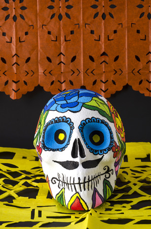 Styrofoam skull with flowers and mustache in a day of the dead offering altar with orange and yellow cut paper Stock Photo