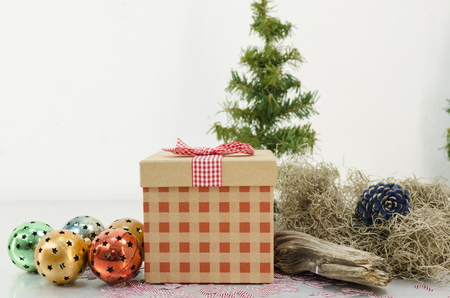 Christmas gift with red ribbon in a composition with Santa Claus hat, christmas tree, christmas balls and bells. Christmas decoration