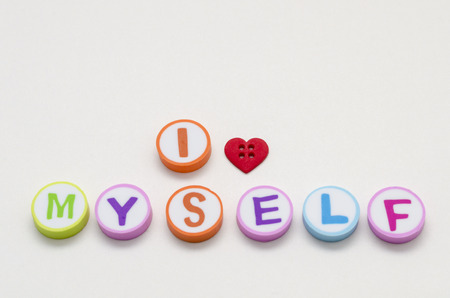 I love myself phrase made from colorful circles with letters and a heart shape button against white background