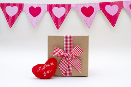Brown gift box with red ribbon, fluffy red heart and hearts party flags against white background