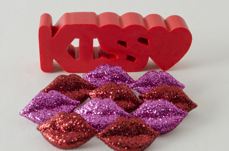 Kiss word in red with a little heart and little shinny red and purple lips against white background