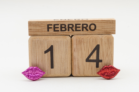 Calendar of rollover cubes with the date of February 14 and little purple and red lips against white background