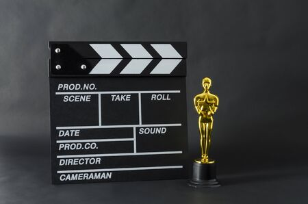 XALAPA, VERACRUZ, MEXICO- FEBRUARY 14, 2019: Plastic Oscar award and clapboard against black background Editorial