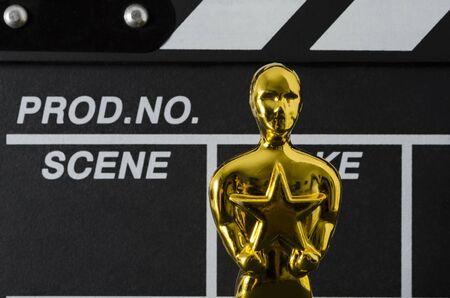 XALAPA, VERACRUZ, MEXICO- FEBRUARY 14, 2019: Plastic Oscar awards, a clapboard and golden stars confetti against black background