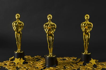 XALAPA, VERACRUZ, MEXICO- FEBRUARY 14, 2019: Plastic Oscar awards and golden stars confetti against black background