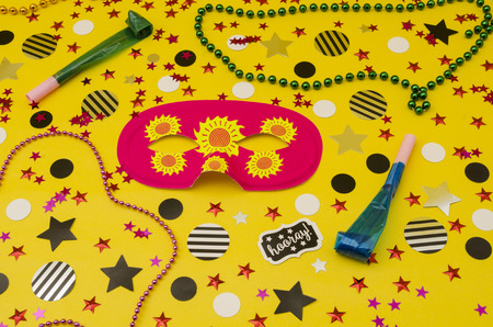 Top view decoration for party. Pink eye mask, plastic necklaces, party blowers and circles and stars confetti on yellow background
