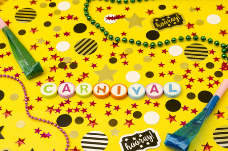 Top view decoration for party. Word carnival made from colorful letters, plastic necklaces, party blowers and circles and stars confetti on yellow background