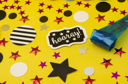 Top view decoration for party. Party blower and circles and stars confetti on yellow background Stockfoto