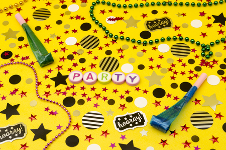 Top view decoration for party. Party word made from colorful letters, plastic necklaces, party blowers and circles and stars confetti on yellow background