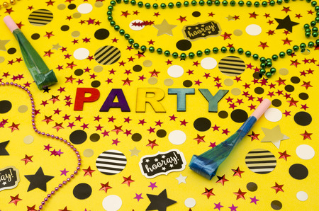 Top view decoration for party. Party word made from colorful wooden letters, plastic necklaces, party blowers and circles and stars confetti on yellow background Standard-Bild