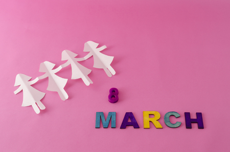 Paper doll chain and march eight made from colorful letters on pink background Imagens