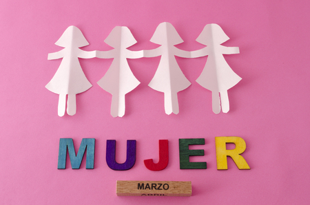 Paper doll chain and mujer made from colorful letters on pink background