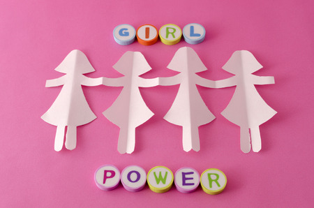Paper doll chain and girl power made from colorful letters on pink background