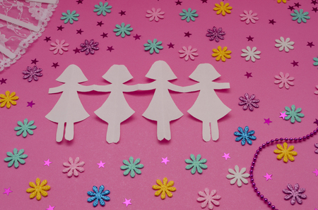 Paper dolls chain, fan and little colorful flowers on pink background. Stockfoto