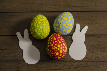 Colorful decorated easter eggs and white paper bunnies on wooden background