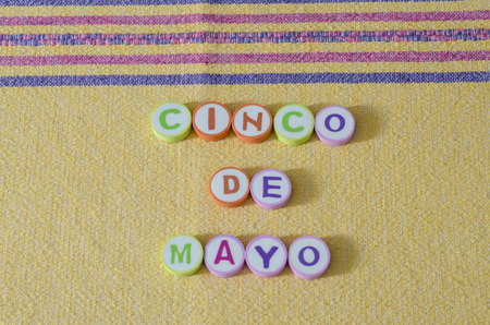 Cinco de Mayo made from colorful letters on yellow tablecloth