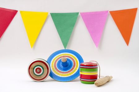 Yo-yo, spinning and balero, wooden mexican toys and colorful flags on white background Imagens