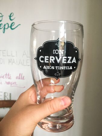 Woman hand holding a glass of beer with the phrase: con cerveza adiós tristeza
