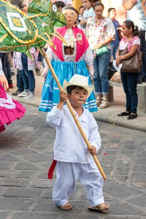 OAXACA, OAXACA, MEXICO- JULY 6, 2019: Little kid carrying a green grasshopper made of cellophane during the Convite, a party made for invite to a big traditional party called Guelaguetza in Oaxaca, Me 報道画像