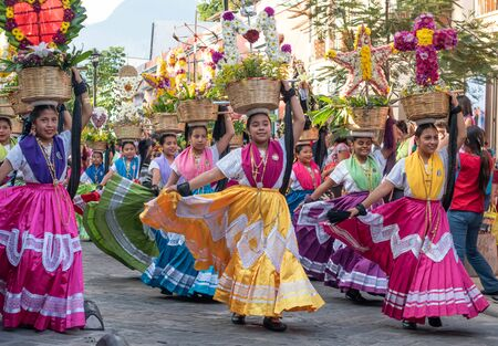 OAXACA, OAXACA, MEXICO- JULY 6, 2019: Young women dressed with traditional clothes during the Convite, a party made for invite to a big traditional party called Guelaguetza in Oaxaca, Mexico