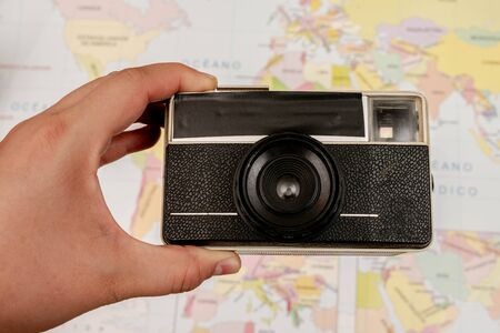 Woman hand holding a vintage camera and a map as background Imagens
