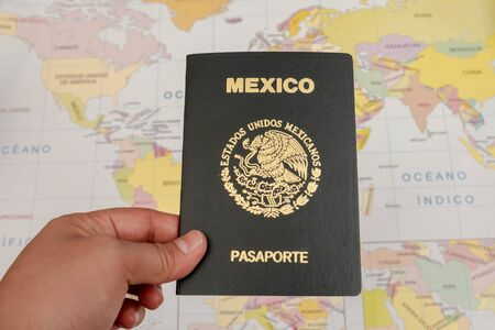 Mano de mujer sosteniendo un pasaporte mexicano con un mapa como fondo