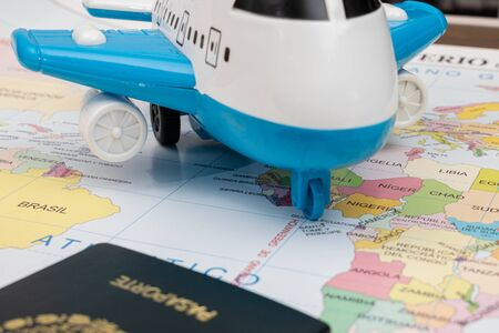 Toy airplane and passport on a map as background
