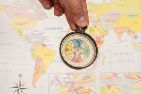 Woman hand holding a colorful compass with a map as background Stok Fotoğraf