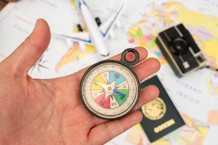 Woman hand holding a compass. A toy airplane, a vintage camera and a mexican passport appear out of focus on a map Stok Fotoğraf