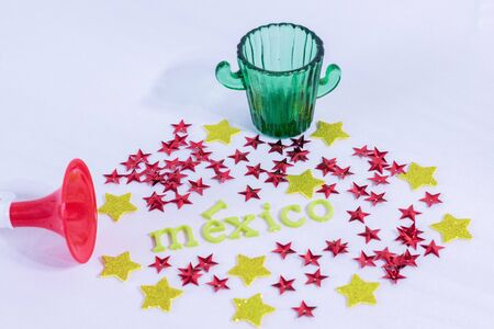 Trumpet, glass of tequila, red and yellow stars and Mexico made from colorful letters on white background